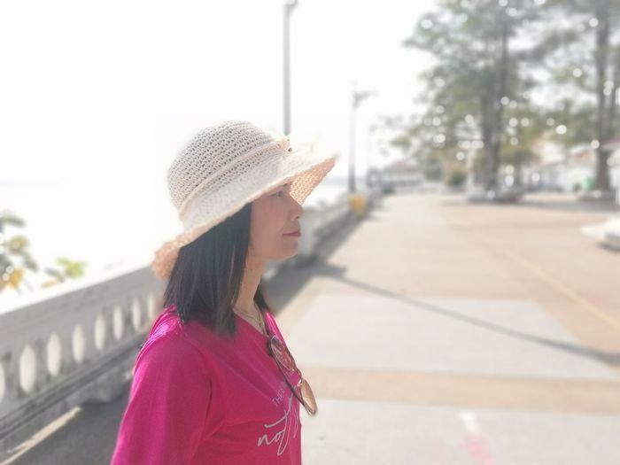 Woman in hat looking away against sea