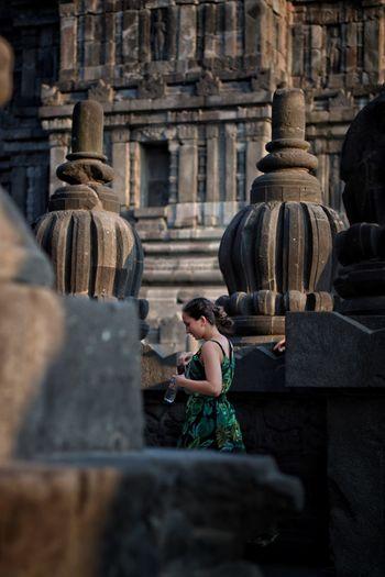 Woman walking amidst old buildings