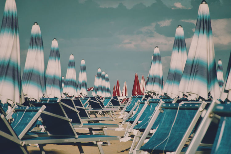 Panoramic view of long chairs and beach umbrellas against sky