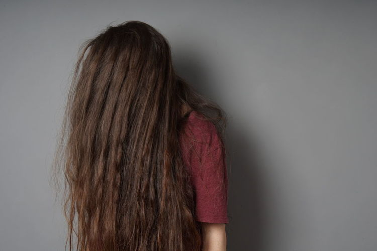 Woman With Long Hair Standing Against Wall