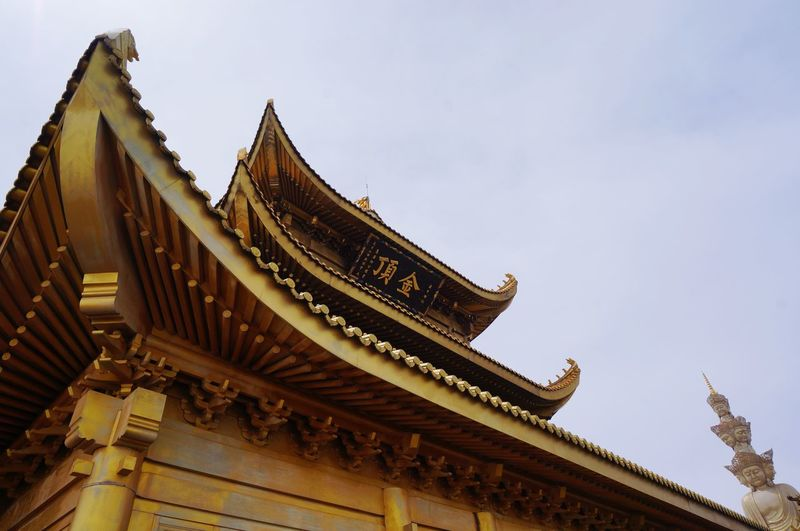 Low angle view of golden summit temple against sky
