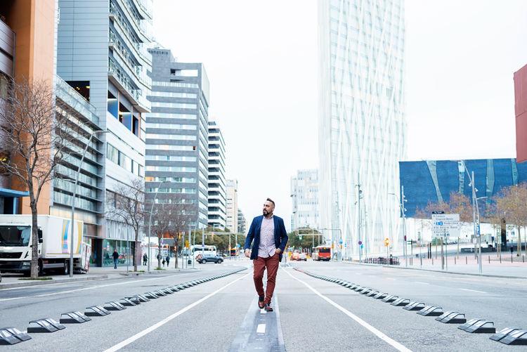 Full length of man walking on street amidst buildings in city