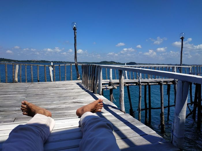 Low section of man relaxing on pier over sea against sky