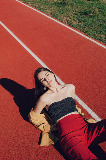 High angle portrait of woman lying down on running track