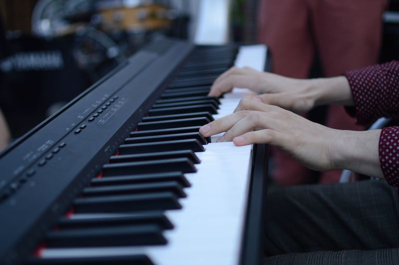 Cropped image of person playing piano