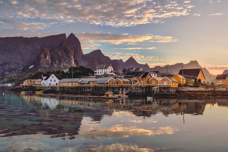 Landscape of Reine in Lofoten, Norway Norway Reine Architecture Beauty In Nature Building Building Exterior Built Structure Cloud - Sky Hamnøy Lake Lofoten Mode Of Transportation Mountain Mountain Range Nature Nautical Vessel No People Outdoors Reflection Scenics - Nature Sky Sunset Transportation Water Waterfront
