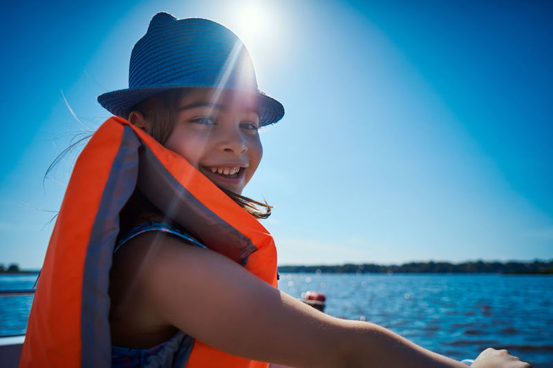 Portrait of cheerful girl wearing life jacket sitting against clear blue sky