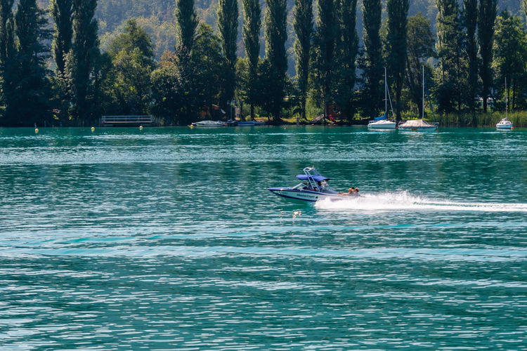 WORTHERSEE, AUSTRIA - AUGUST 08, 2018: View from the boat to the lake and coastline. Local residents and tourists swim, driven by motorboats and use other forms of water recreation. Nature Day Outdoors Austria Carinthia Carinthian Lakes Tourist Tourists Lake Wörthersee Recreation  Leisure Landscape Water Sea Boats Motorboat Speedboats Summer People Holidays Fun Travel Beach Resort Lifestyle Sunny Rest Joy Waves Europe Alps Alpine Alpine Lake Nautical Vessel Waterfront Transportation Mode Of Transportation Real People Motion Men Tree Leisure Activity Lifestyles Speed Sport Plant Beauty In Nature Jet Boat Riding