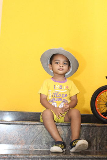 Portrait of boy sitting against yellow wall