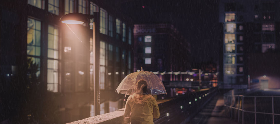 Rear view of woman holding umbrella while walking on footbridge
