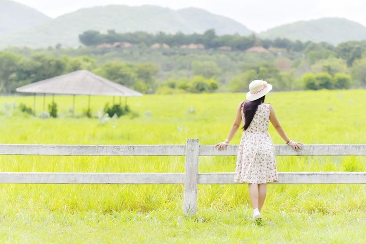 Rear View Of Woman Standing At Fence On Grassy Field Against Mountains