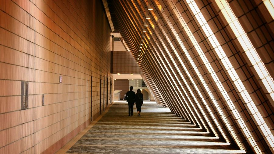 Full length rear view of man and woman walking in building corridor