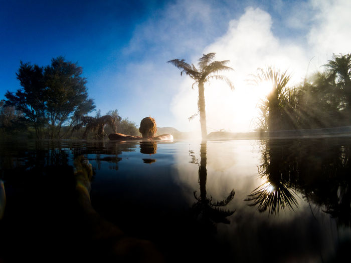 young woman in a hot pool in new zealand Palm Tree Travel Beauty In Nature Cloud - Sky Day Digital Composite Hot Spring Lake Nature New Zealand No People Non-urban Scene Outdoors Palm Tree Plant Reflection Scenics - Nature Sky Spa Tranquil Scene Tranquility Tree Tropical Climate Water Waterfront The Traveler - 2018 EyeEm Awards Summer Road Tripping