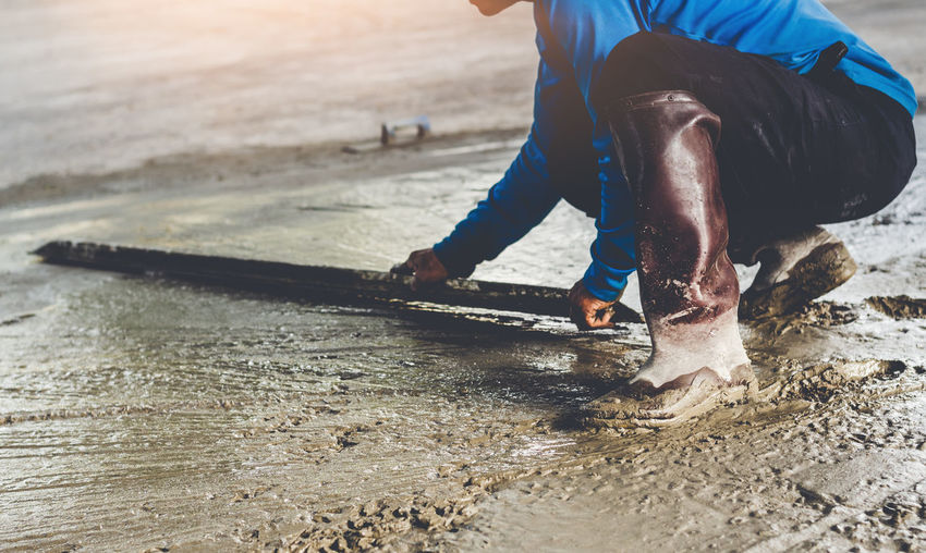 One Person Water Real People Low Section Day Nature Men Occupation Lifestyles Focus On Foreground Human Body Part Human Leg Body Part Outdoors Beach Sunlight Working Wet