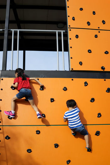 Low Angle View Of Children Climbing Wall