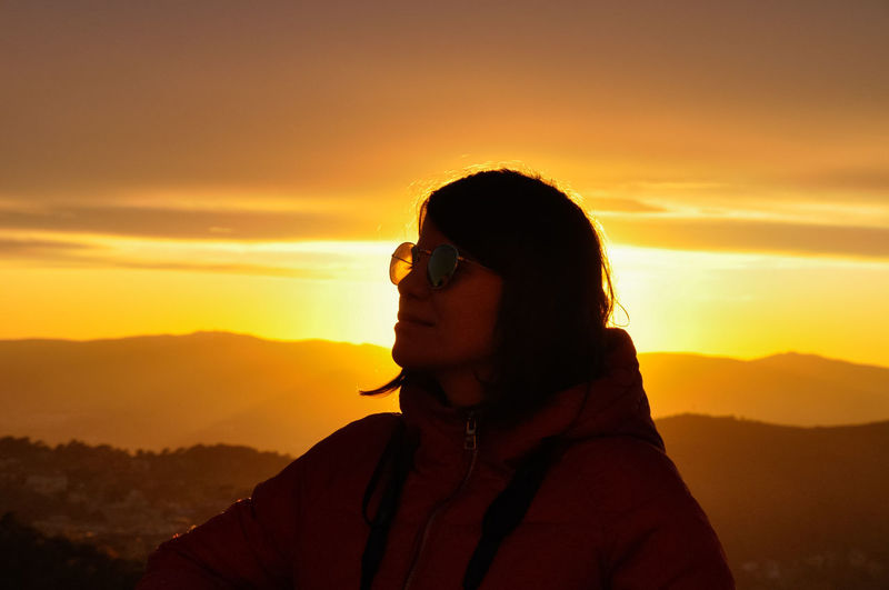 Close-up of young woman wearing sunglasses against orange sky