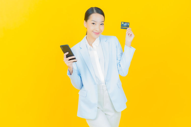 Woman holding smart phone while standing against yellow background