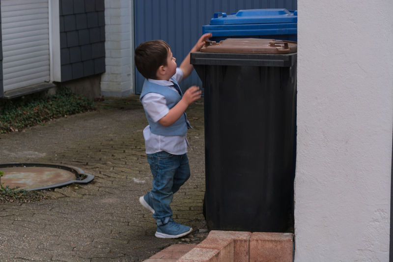 Full length of boy opening garbage bin while standing on footpath