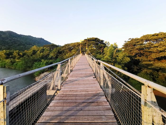 Footbridge leading to mountains against sky