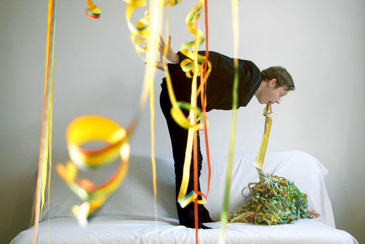 Man exhaling multi colored decoration on bed