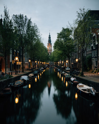 A calm evening by the river in amsterdam, netherlands, with the lights illuminating.