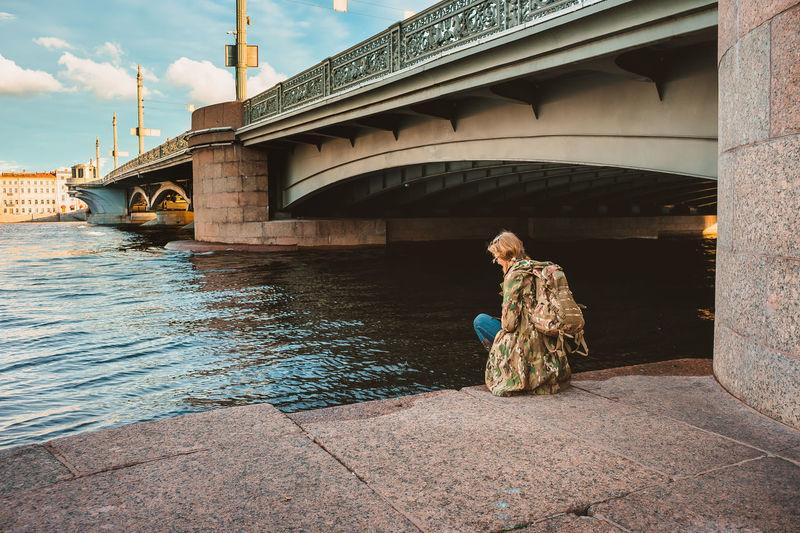 Man sitting on bridge over river against sky