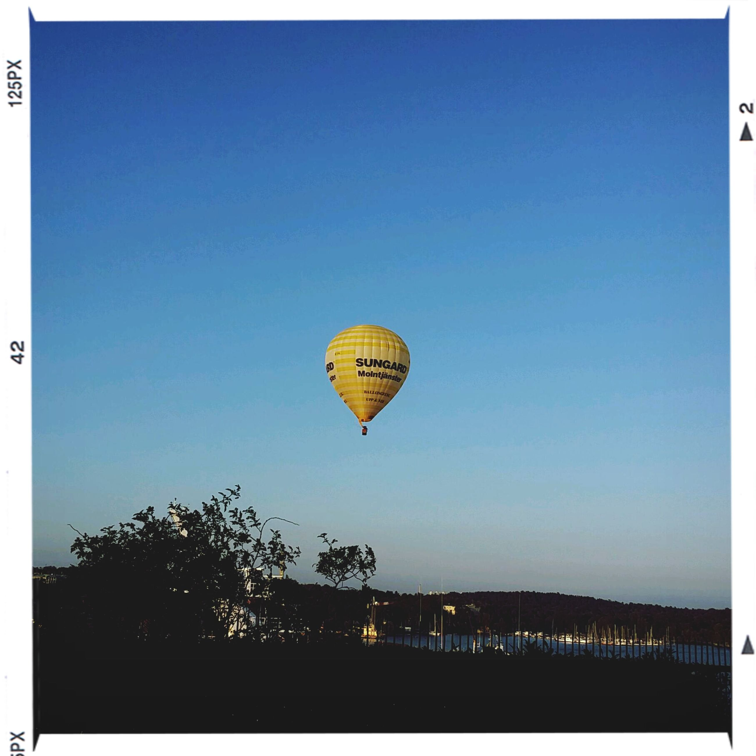 clear sky, transfer print, copy space, auto post production filter, blue, transportation, flying, low angle view, outdoors, built structure, mid-air, illuminated, hot air balloon, tree, sky, architecture, no people, building exterior, day, travel