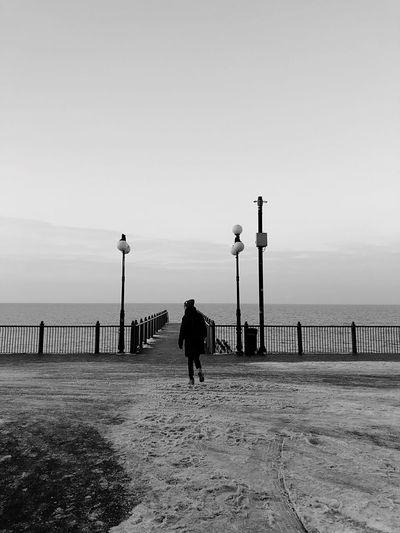 Rear view of woman walking towards sea against clear sky