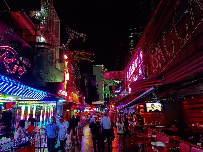 People on illuminated street amidst buildings at night