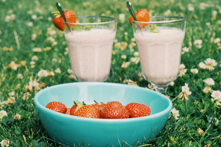 Close-up of strawberries in bowl with drinks