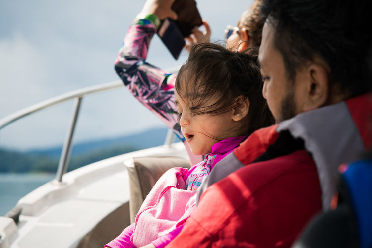 Cute girl with father sitting on boat