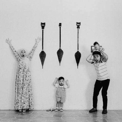 Full length of children standing against wall