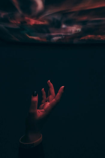 Close-up of woman hand against sea at night