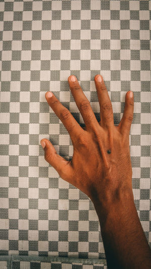 Cropped hand of man touching checked pattern tablecloth
