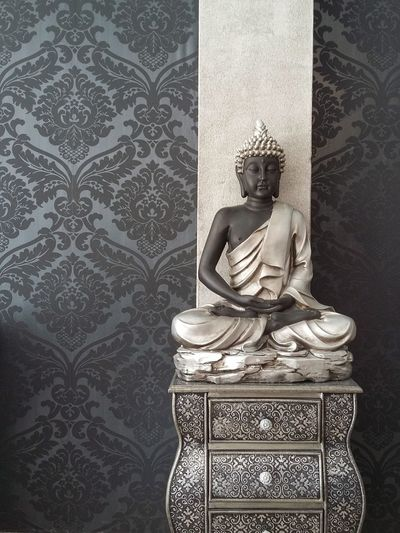 Buddha statue on cabinet by wall