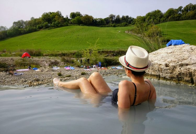 woman enjoys the free spas of Saturnia Hat Water Real People Nature Sun Hat Outdoors Weekend Activities Holiday Vacations Lifestyles Day One Person Trip Thermal Free Wellness Treatment Therapy Woman Adult