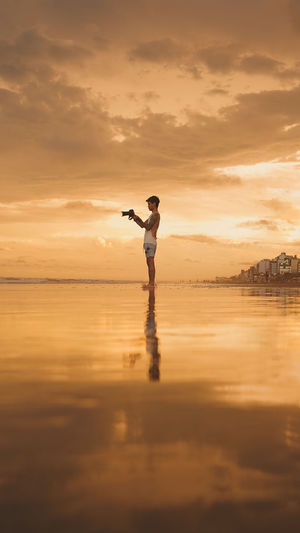 Full length of man standing at beach during sunset