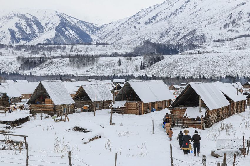 Hemu, Xinjiang - February 16, 2018: Local people walking towards the Hemu Village in northern Xinjiang ASIA Altai Mountains Bactrian Camel Ice Kanas Lake Urumqi XinJiang Altai China Grassland Hasake Minority Hemu Village Horse Racing Kanas Ski Country Snow Tuva Minority
