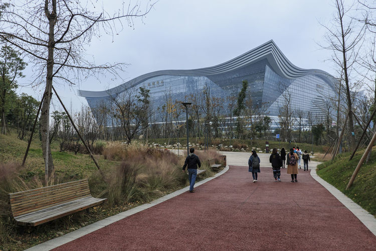 Chengdu, China - December 10, 2018: People walking towards the New Century Global Center, the biggest mall in the world in terms of square meters Chengdu China ASIA New Century Global Center Mall Shopping Center Group Of People Tree Plant Real People Store