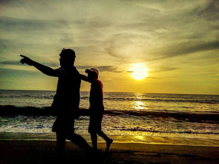 Silhouette couple standing at beach during sunset