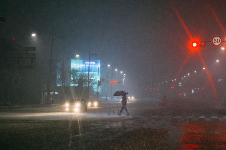 Man on illuminated street at night
