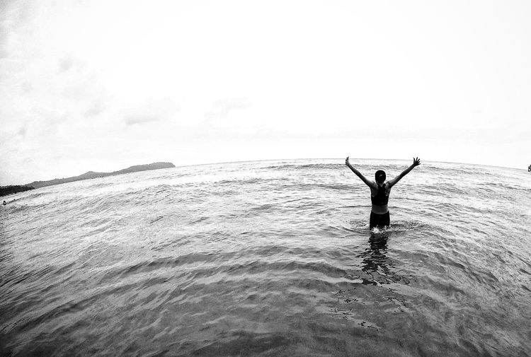 Rear View Of Young Woman With Arms Raised Standing In Sea Against Sky