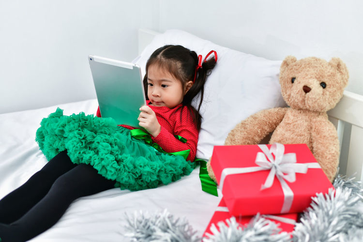 Cute Girl Using Digital Tablet While Lying By Christmas Gift And Teddy Bear In Bed At Home