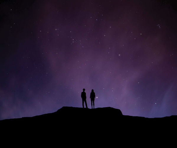 Low Angle View Of Silhouette Man And Woman Standing On Cliff Against Star Field