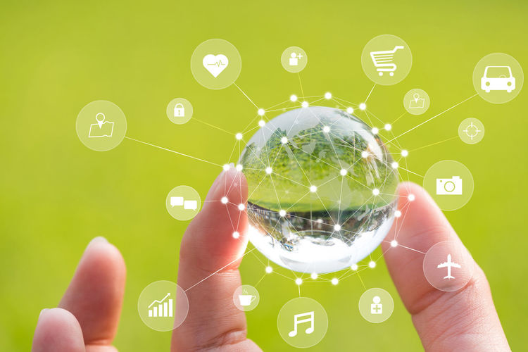 Digital composite image of cropped hand holding crystal ball by icons