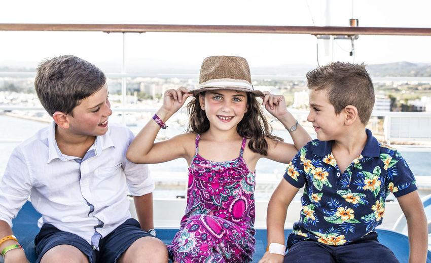 Three little friends Bonding Casual Clothing Child Childhood Clothing Day Emotion Front View Girls Group Of People Hairstyle Happiness Hat Leisure Activity Men Outdoors Real People Sitting Smiling Teenage Boys Three Quarter Length Togetherness
