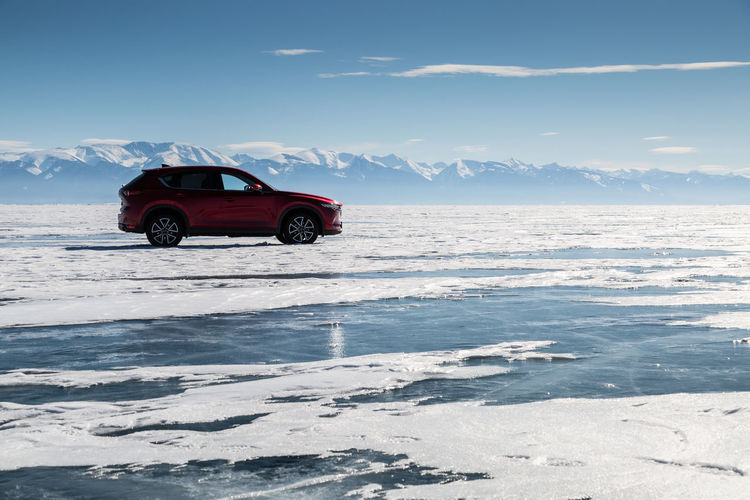 Red car on snow covered sea against sky
