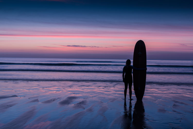 Surfer on beach at sunset Adult Beach Beach Life Calm Coastline Full Length Horizon Over Water Nature One Person Outdoors Peaceful Sea Seascape Silhouette Sky Standing Sunset Surfboard Surfer Tranquil Scene