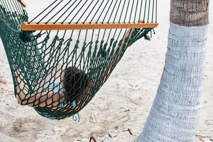 Woman lying on hammock at beach