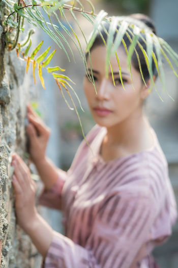 Portrait of young woman by wall and plants